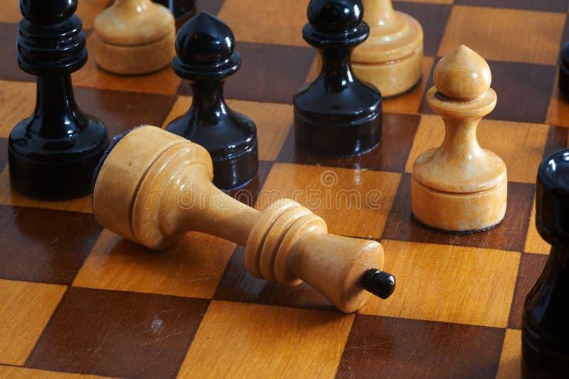 Le roi blanc d'échecs abandonne sur l'échiquier images libres de droits