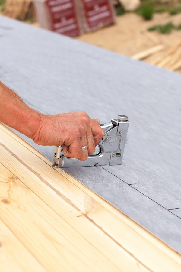 Le Roofer cloue la doublure utilisant l'agrafeuse de construction Toit en construction image stock