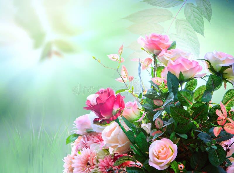 Le rose artificiali fiorisce la disposizione del mazzo contro sfuocatura verde immagine stock
