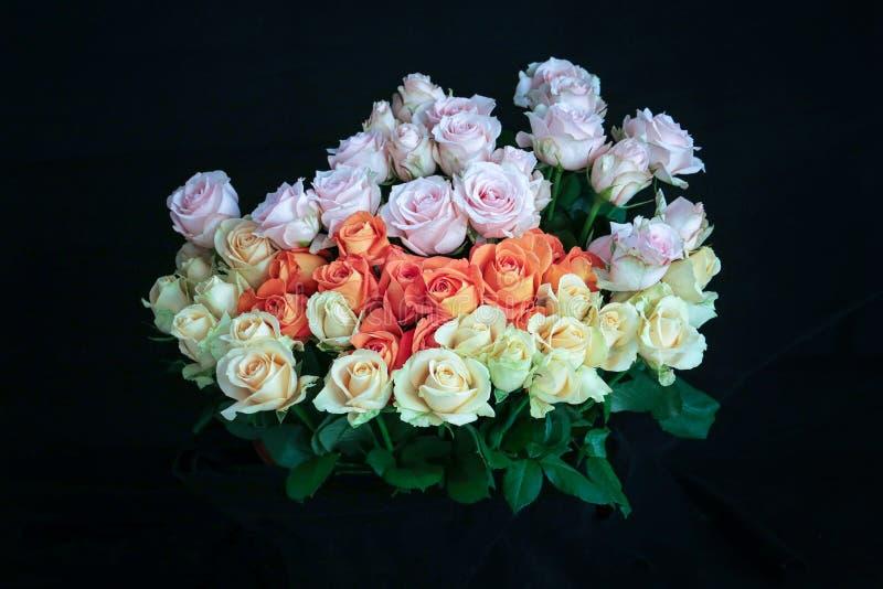 Le rose bianche rosa arancioni Handbouquet con fondo ed il dettaglio neri della rugiada sulle rose fanno le rose guardano così be immagini stock