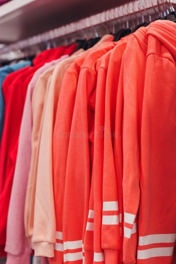 Le rose des femmes faire semblent le coup mince sur un cintre Vente des vêtements dans le magasin images libres de droits
