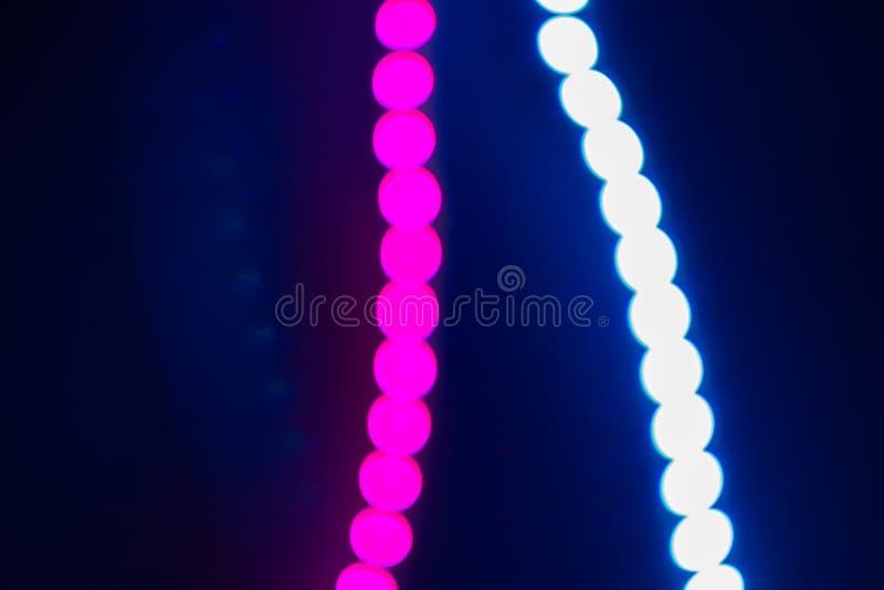 Le rose et le néon trouble bleu ont mené des lumières de bande sur le noir Fond abstrait de couleurs 80s photo libre de droits