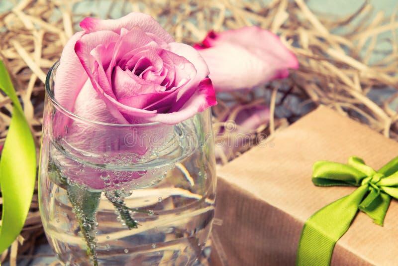 Le rose a monté dans un verre avec de l'eau et des décorations sur la table photo libre de droits