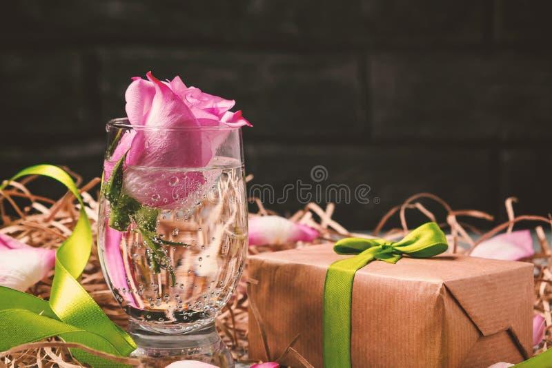 Le rose a monté dans un verre avec de l'eau et des décorations sur la table photographie stock libre de droits