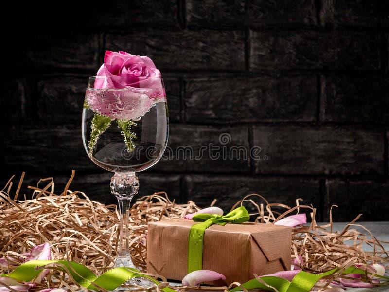 Le rose a monté dans un verre avec de l'eau et des décorations sur la table image stock