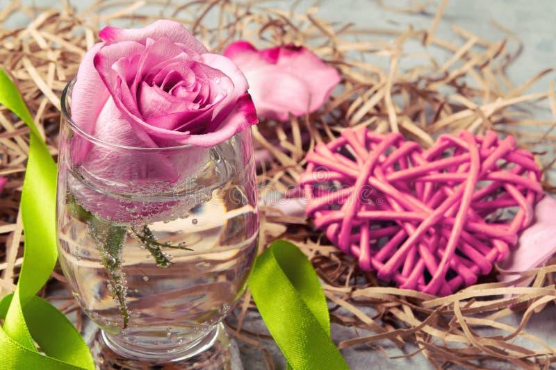 Le rose a monté dans un verre avec de l'eau et des décorations sur la table image libre de droits