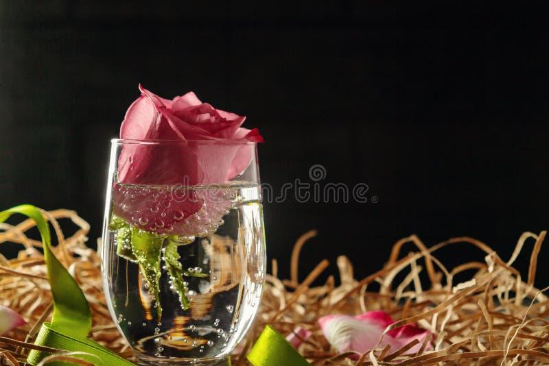 Le rose a monté dans un verre avec de l'eau et des décorations sur la table photos libres de droits
