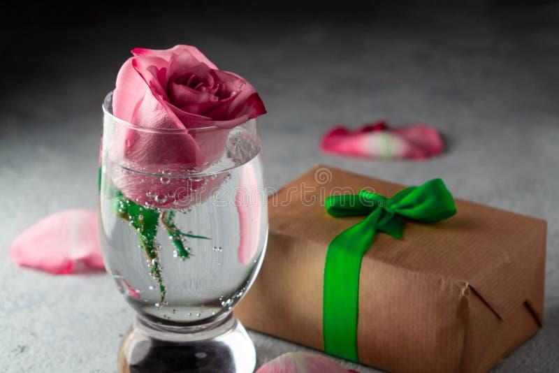 Le rose a monté dans un verre de l'eau, des pétales de rose et d'une boîte avec un cadeau sur la table photographie stock libre de droits