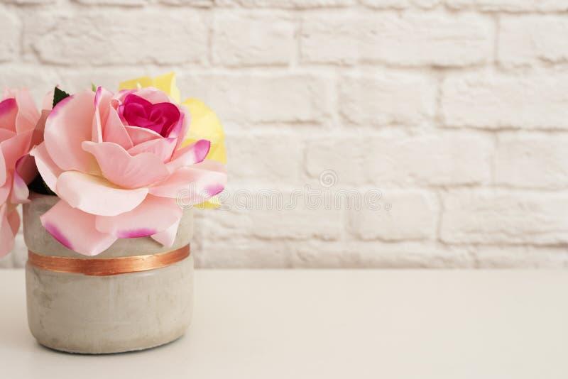 Le rose rosa deridono su Fotografia disegnata Esposizione del prodotto del muro di mattoni Scrittorio bianco Vaso con le rose den fotografie stock