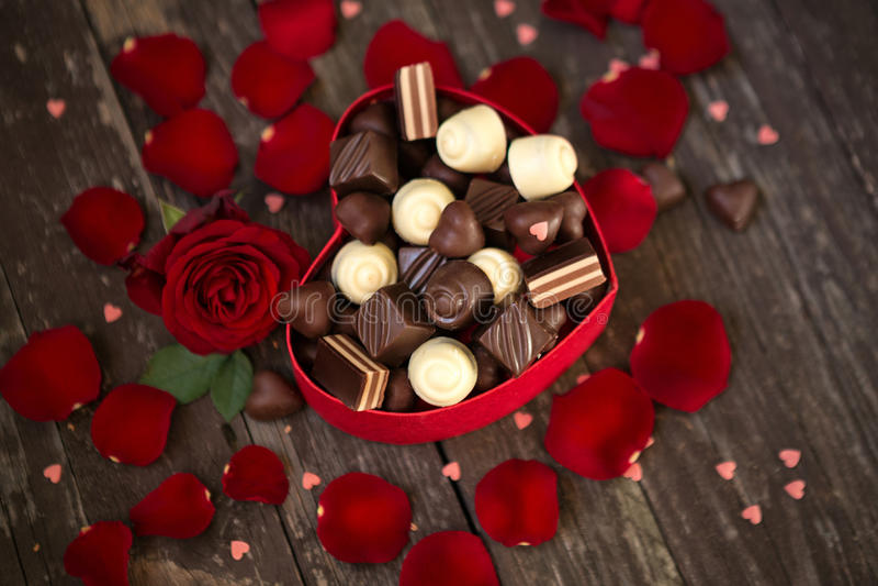 Le rose rosse e le praline del cioccolato nel cuore hanno modellato il contenitore di regalo immagine stock libera da diritti