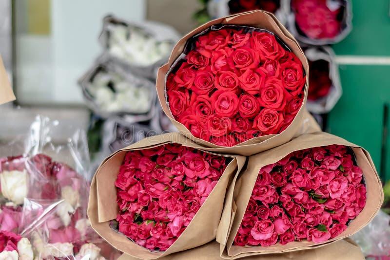 Le rose rosse e rosa imballate fioriscono con la carta crema di colore sono vendute in Pak Klong Market Bangkok immagini stock