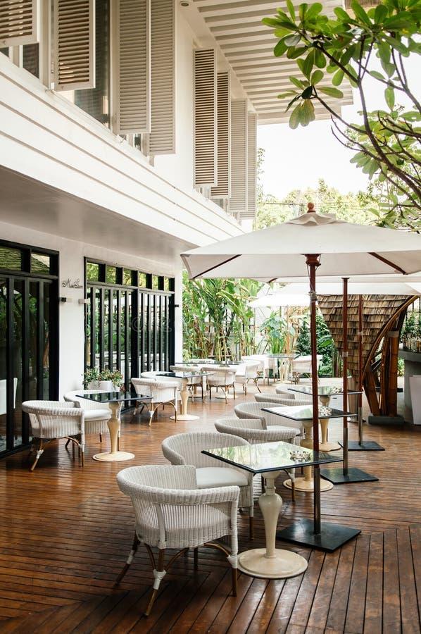Le rotin préside les parapluies de table de salle à manger et blancs en pierre au balcon photo libre de droits