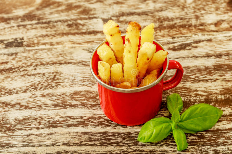 Le rouge a émaillé la tasse avec des fritures de pomme de terre décorées de deux tomates-cerises, au-dessus de table en bois Vue  image stock