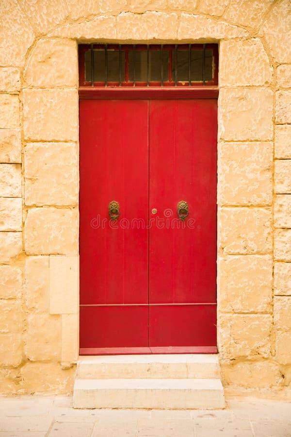 Le rouge a coloré la porte en bois, mur en pierre de sable dans la ville de la Médina, Malte photos libres de droits