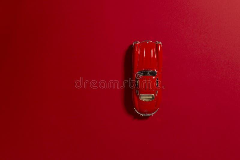 Le rouge a coloré le produit de voiture modèle de jouet tiré sur un fond rouge photographie stock