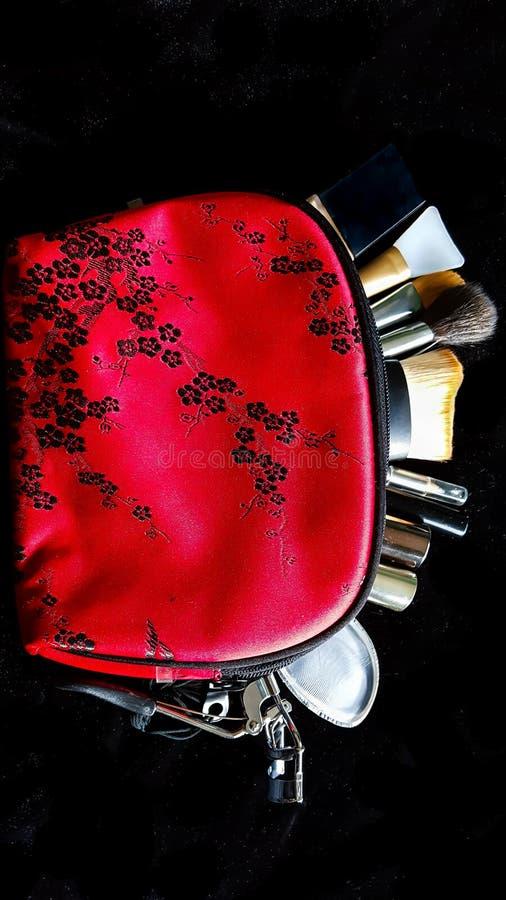 Le rouge composent le sac avec des brosses dans lui images libres de droits
