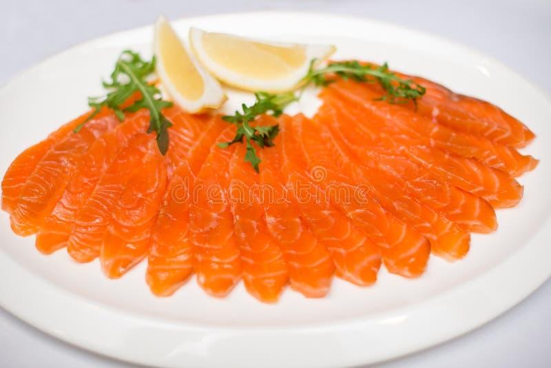 Le rouge a découpé des poissons en tranches sur le withlemon de plat sur le fond blanc photo libre de droits