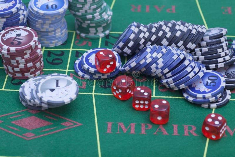 Le rouge découpe des puces d'extrémité sur une table de jeu dans un casino image stock