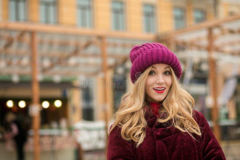 Le rouge de port étonné de jeune femme a tricoté le chapeau et le manteau d'hiver, p images libres de droits
