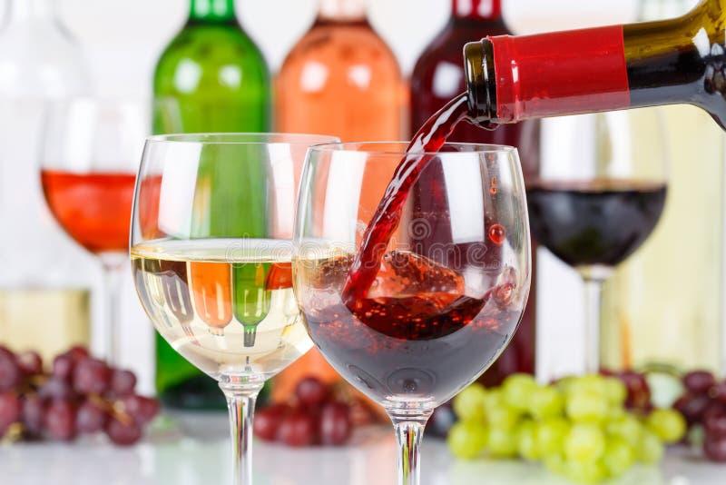 Le rouge de versement de bouteille en verre de vin versent photographie stock libre de droits