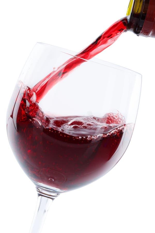 Le rouge de versement de bouteille en verre de vin versent le format de portrait d'isolement sur W photos libres de droits