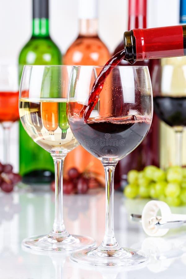 Le rouge de versement de format de portrait de bouteille en verre de vin versent photo libre de droits