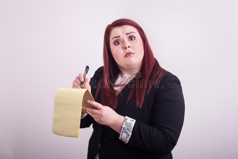 Le rouge a dirigé le costume de port femelle prenant des notes sur le bloc-notes jaune photo stock