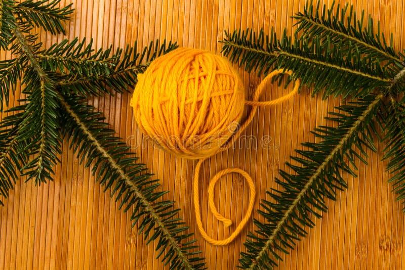 Le rouleau de fil à tricoter mou jaune et l'if s'embranchent photo stock