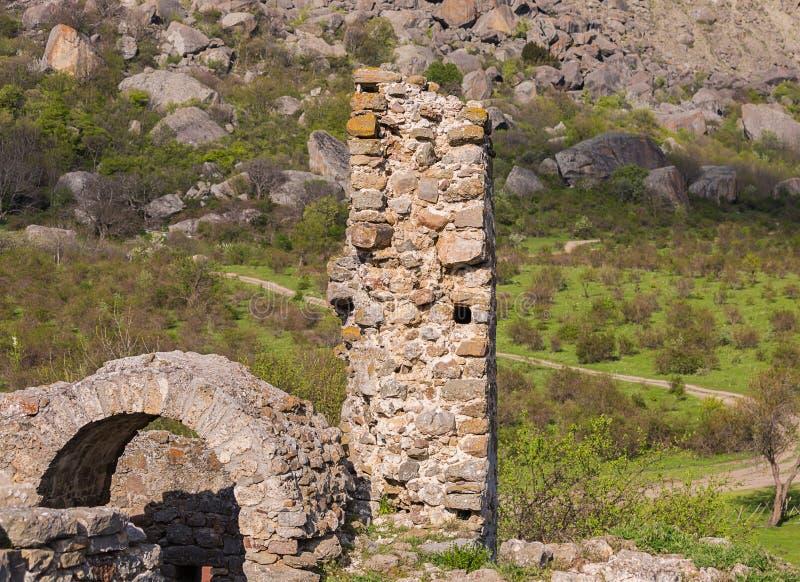 Le rovine del castello, elementi delle costruzioni incurvano la pietra della colonna sui precedenti delle alte montagne sotto col immagini stock