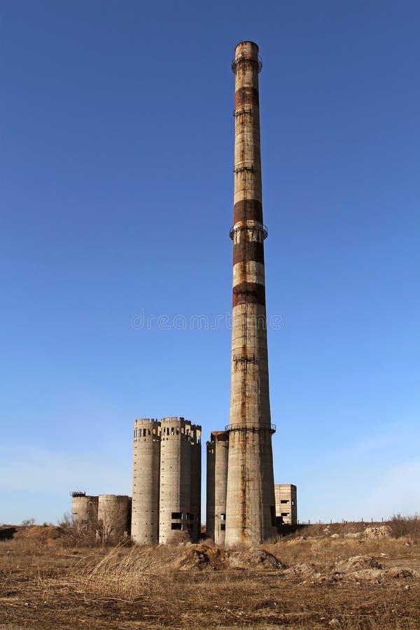 Le rovine della fabbrica distrutta con un camino alto riparato dentro fotografie stock libere da diritti