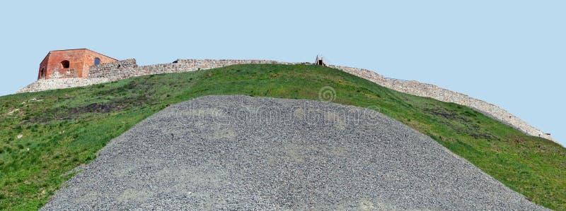 Le rovine di una parete antica della fortezza su una collina erbosa contro il cielo blu fotografia stock