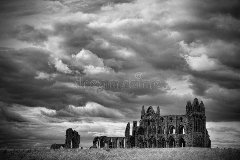 Le rovine di Whitby Abbey con il contesto nuvoloso drammatico immagini stock libere da diritti