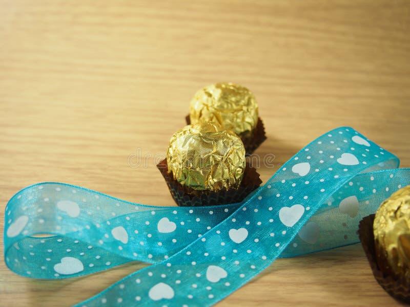 Le ruban de ciel bleu avec la forme de coeur, boules de chocolat, a couvert l'aluminium d'or images stock
