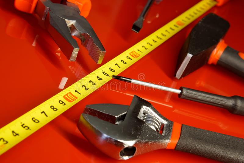 Le ruban métrique, le tournevis, le marteau, les pinces et d'autres outils se trouvent sur une surface polie rouge dans un atelie photos libres de droits