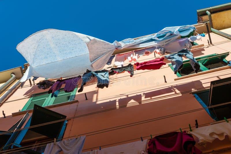 Le séchage lavé de blanchisserie a suspendu sur le mur de la maison photographie stock libre de droits