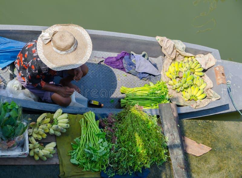 Le séjour de vieille dame sur son bateau et vendent un certain légume local et un groupe de banane, près d'un pilier en Thaïlande images stock