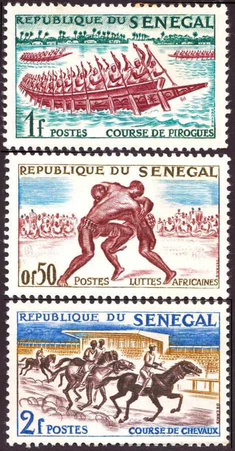LE SÉNÉGAL - VERS 1961 : les timbres imprimés au Sénégal montre des concours dans des sports nationaux, vers les années 1960 photo stock