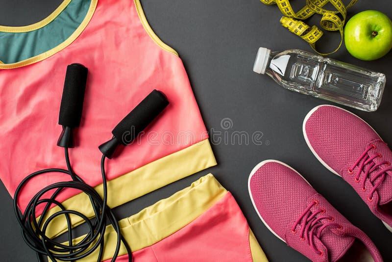 Le ` s d'athlète a placé avec l'habillement, les espadrilles et la bouteille femelles de l'eau sur le fond gris photo stock