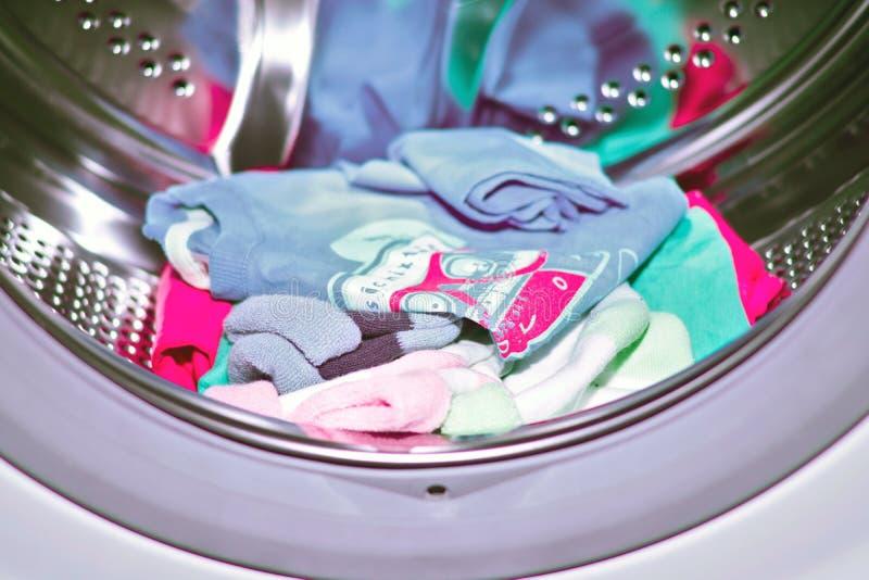 Le ` s d'enfants a coloré des choses dans le fût de la machine à laver automatique, lavage de maison des choses image libre de droits