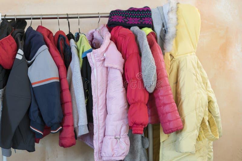 Le ` s d'enfants d'hiver vêtx accrocher sur un cintre image stock