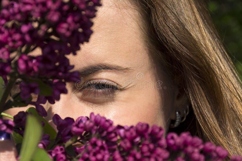 Le ` s de femme observe, la fille parmi les fleurs du lilas image libre de droits