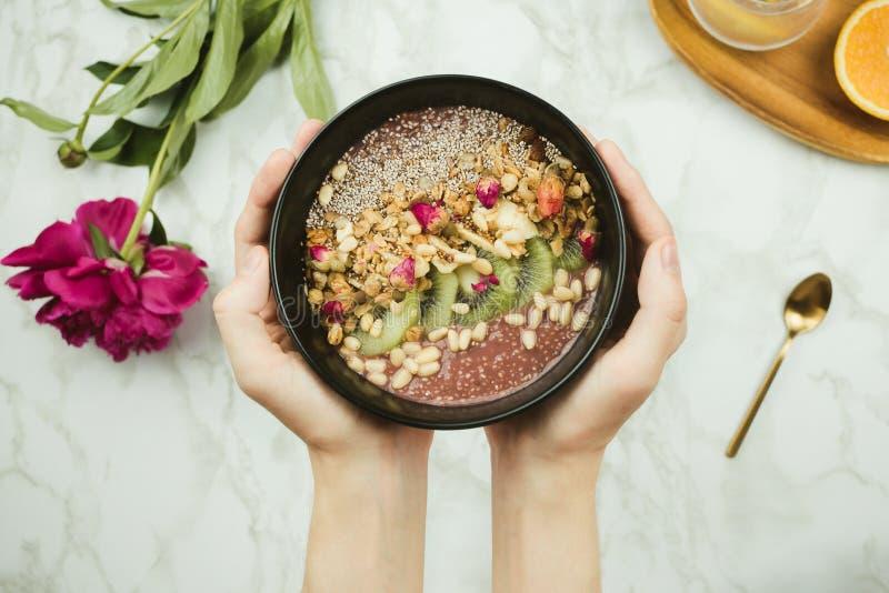 Le ` s de femme remet tenir le bol de smoothie de vegan avec le pudding de chia complété avec la granola photo stock