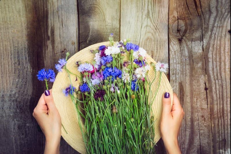 Le ` s de femme de vue supérieure remet tenir le chapeau de paille et le bouquet romantique de groupe de sauvage-fleur sur le fon photos libres de droits