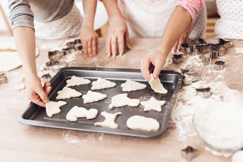 Le ` s de femmes et les mains du ` s d'enfants présentent des biscuits de biscuit pour le deco dans la cuisine image stock