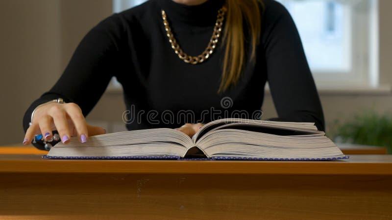 Le ` s de femmes remet la feuillaison par un livre Femme s'asseyant à la table poussant des feuilles par le livre images stock