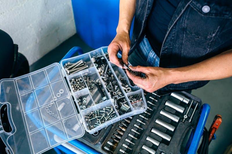 Le ` s de mécanicien remet choisir des vis d'une boîte à outils photographie stock