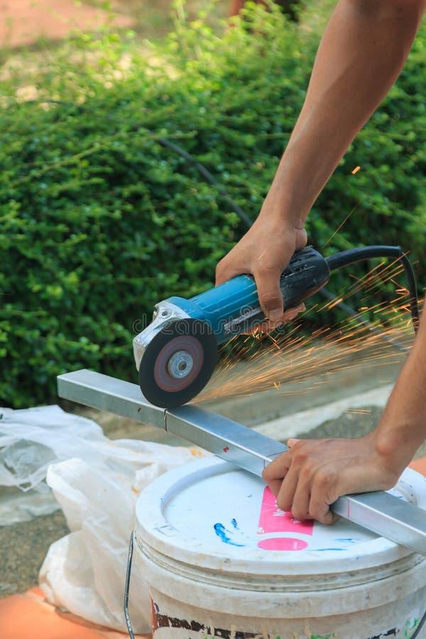 Le ` s de travailleur de la construction remet à coupe le cadre en aluminium avec la broyeur d'angle photographie stock