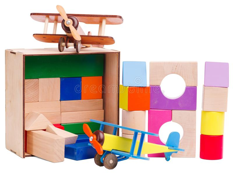 Le ` s en bois, formes géométriques d'enfants, empilées sur l'un l'autre, avec un avion modèle, a isolé sur le fond blanc photographie stock