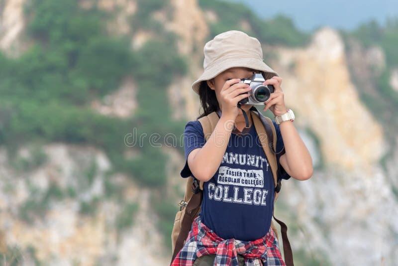 Le sac à dos de fille d'enfants caucasiens et l'appareil-photo asiatiques de sourire heureux de se tenir pour prennent une photo  image libre de droits