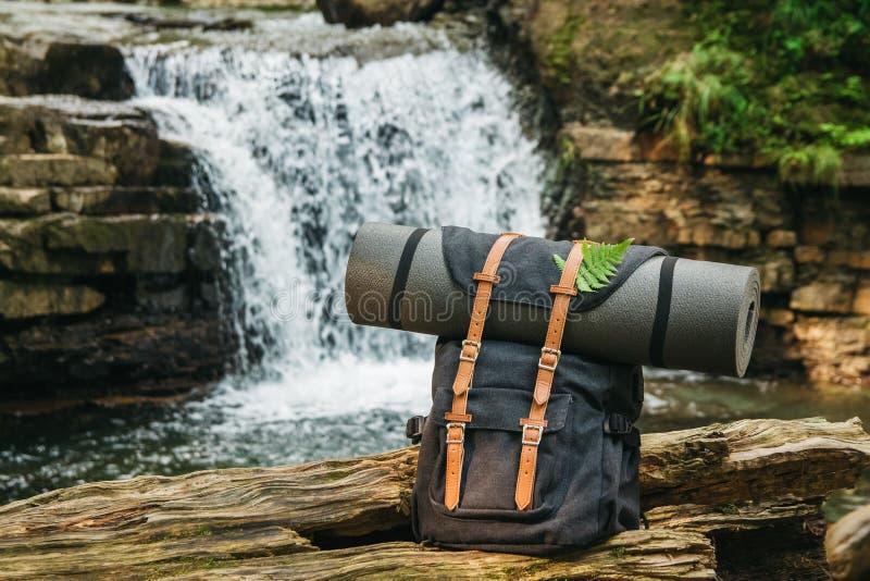 Le sac à dos de touristes de randonneur de hippie sur le fond de la rivière et de la cascade, voyageur détendent le concept de va photo libre de droits